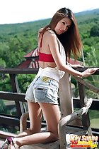 Kneeling on wooden chair looking over her shoulder long hair wearing denim shorts