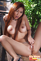 Seated topless long hair between her big breasts legs open pulling panties taut over her pussy