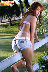 Sitting Astride Fence Looking Back Wearing Shorts