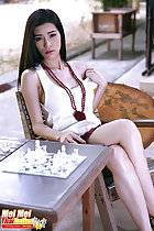 Mei Mei sitting on chair beside chess board