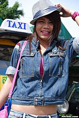 Standing On Front Of Taxi Adjusting Her Hat Wearing Denim Jacket