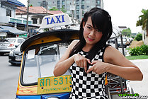 Standing in front of taxi wearing checkerboard outfit making heart symbol